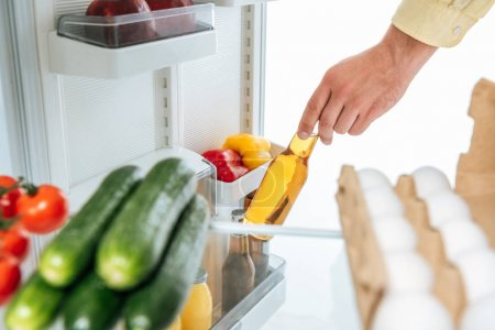 Photo pour Cropping view of man taking bottle of beer out from fridge with fresh food on shelves isolated on white - image libre de droit
