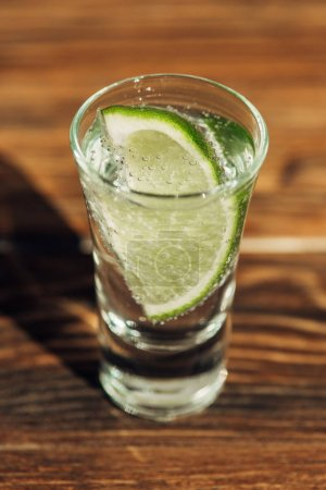 Photo pour Vue de près de la tequila fraîche avec chaux sur la surface de bois au soleil - image libre de droit