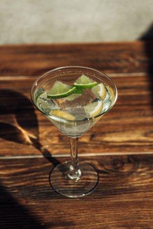 Photo pour Verre de margarita avec glace, citron et limette décoré de sucre sur une surface en bois au soleil - image libre de droit
