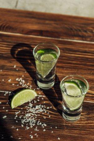 Photo pour Tequila fraîche avec chaux et sel sur une surface en bois exposée au soleil - image libre de droit