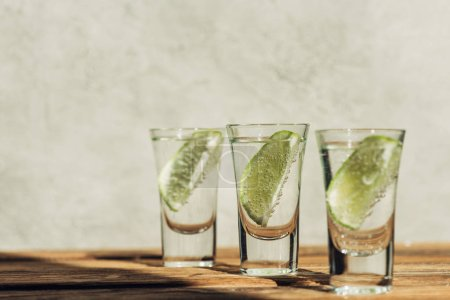 selective focus of fresh tequila with lime on wooden surface in sunlight