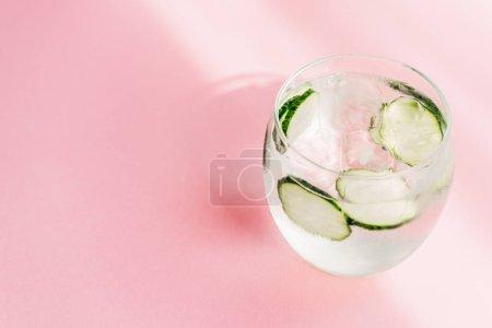 Photo pour Limonade fraîche avec glace et tranches de concombre sur fond rose avec lumière du soleil - image libre de droit