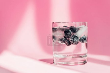 fresh lemonade with ice and blueberries in sunlight on pink background