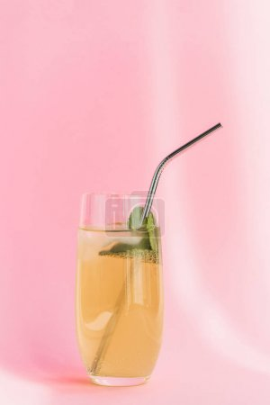 fresh lemonade with ice, straw and mint in sunlight on pink background