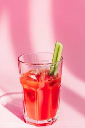 Photo pour Mary rouge sanglante fraîche avec céleri au soleil sur fond rose - image libre de droit