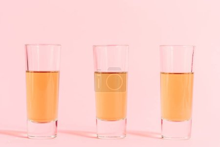 three shots with alcohol in row on pink background