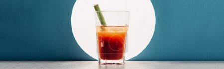 bloody Mary with celery on blue background with back light, panoramic shot