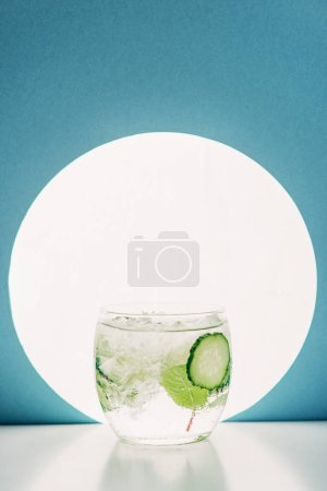 Foto de Fresh gin and tonic with cucumber slices on blue background with back light - Imagen libre de derechos