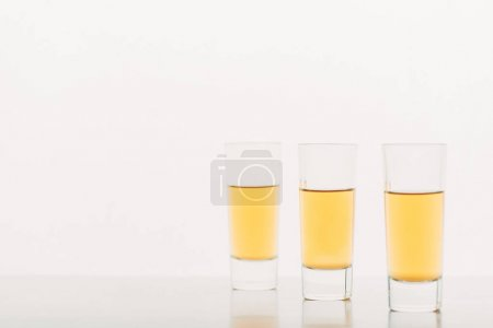 three shots with alcohol in row isolated on white