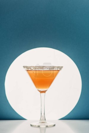 Foto de Cóctel fresco en vaso de martini sobre fondo azul con luz de fondo - Imagen libre de derechos