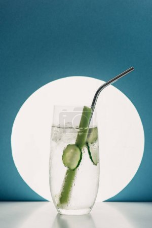 Photo for Fresh lemonade with cucumber slices, celery and straw on blue background with back light - Royalty Free Image