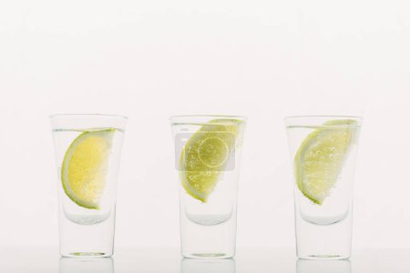 fresh tequila with lime in row isolated on white
