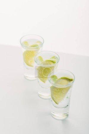 Photo pour Tequila fraîche à la chaux en rangée isolée sur blanc - image libre de droit