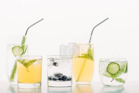 refreshing drinks with blueberries, celery, straws, mint, cucumber and ice isolated on white