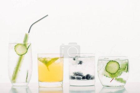 Photo pour Boissons rafraîchissantes avec bleuets, céleri, paille, menthe, concombre et glace isolés sur blanc - image libre de droit