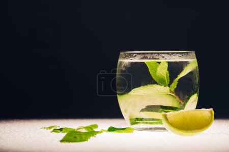 Photo for Refreshing lemonade with mint, cucumber and lime on illuminated surface isolated on black - Royalty Free Image