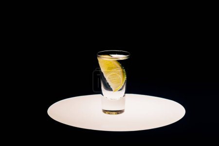 Photo for Fresh tequila with lime on illuminated circle isolated on black - Royalty Free Image