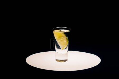 Photo pour Tequila fraîche à la chaux sur cercle éclairé isolé sur noir - image libre de droit