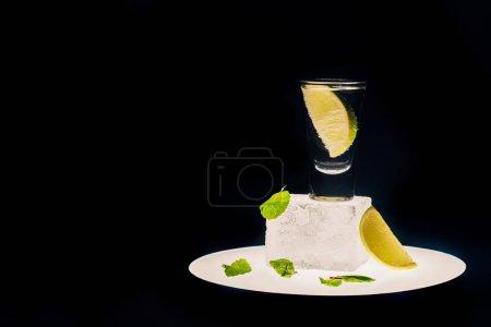 Photo pour Tequila fraîche avec chaux et menthe sur cube de glace sur cercle éclairé isolée sur noir - image libre de droit