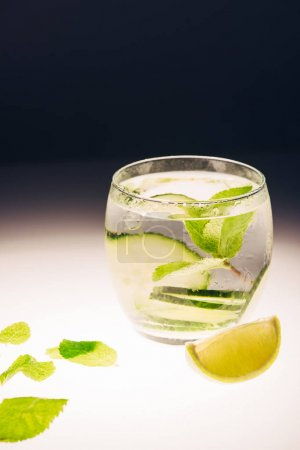 Photo for Refreshing lemonade with mint, cucumber and lime on illuminated surface on black background - Royalty Free Image