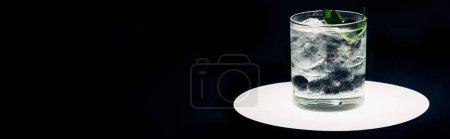 Photo for Refreshing lemonade with ice and blueberries on illuminated circle isolated on black, panoramic shot - Royalty Free Image