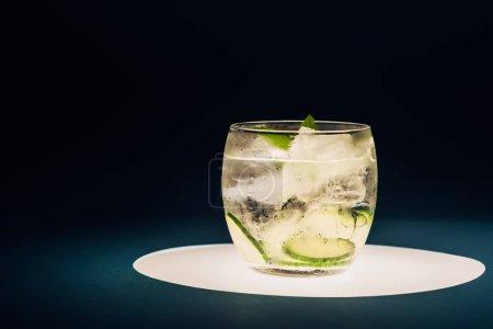 Photo pour Limonade rafraîchissante à la menthe, concombre et glace sur cercle éclairé isolé sur noir - image libre de droit