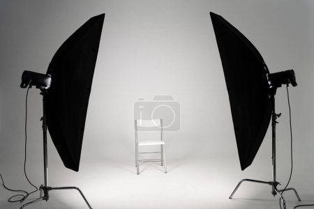White chair with studio light on grey background