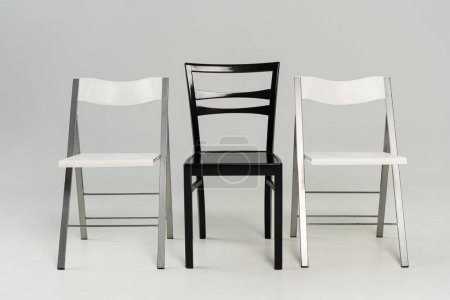 Photo for Three black and white chairs on grey background - Royalty Free Image