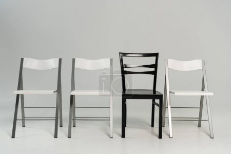 Photo for Empty black and white chairs on grey background - Royalty Free Image