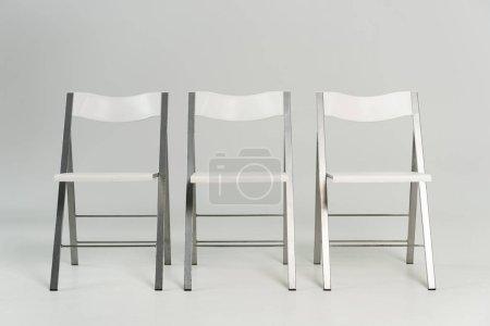 Foto de Tres sillas blancas modernas con fondo gris - Imagen libre de derechos