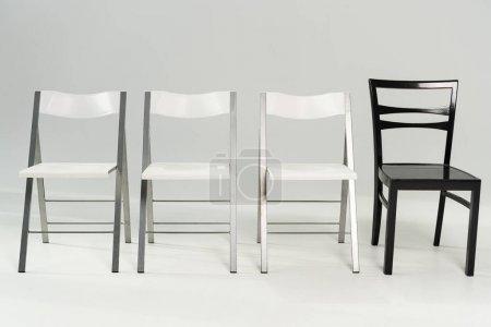 Photo pour Chaises modernes blanches et noires sur fond gris - image libre de droit