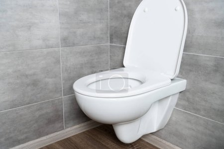 Clean toilet bowl with open seat in modern bathroom with grey tile