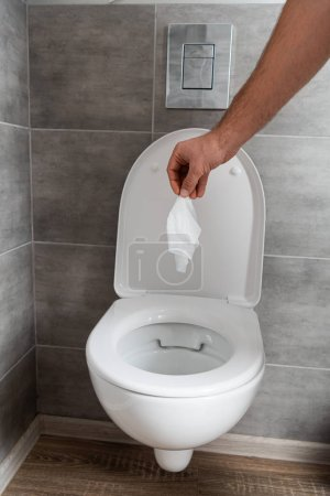 Cropped view of man holding napkin above toilet bowl