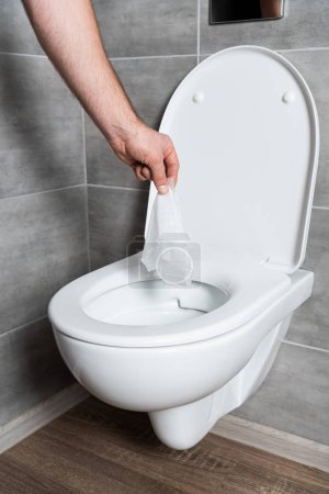Cropped view of man throwing napkin in clean toilet bowl at bathroom