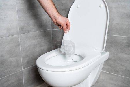 Photo pour Vue croustillante d'un homme lançant une serviette dans une cuvette de toilette dans la salle de bain avec tuile grise - image libre de droit