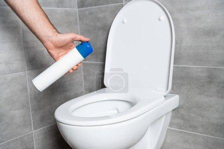 Foto de Vista cruzada del hombre que tiene aire fresco encima de la taza de aseo en el cuarto de baño con azulejos gris. - Imagen libre de derechos