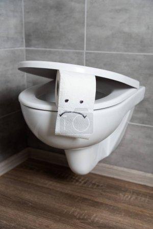 Sad emoticon on white toilet paper on toilet bowl in modern restroom