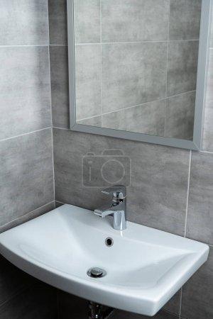 Foto de Lavamanos cerámicos con espejo en lavadero moderno con azulejos grises. - Imagen libre de derechos