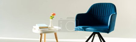 Photo for Panoramic shot of blue armchair by coffee table with flower in vase and books on grey background - Royalty Free Image