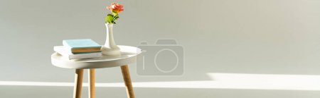 Photo for Panoramic shot of coffee table with rose in vase and books on grey background - Royalty Free Image
