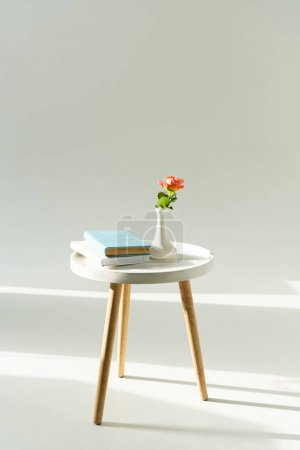 Photo for Trendy coffee table with flower in vase and books on grey background - Royalty Free Image