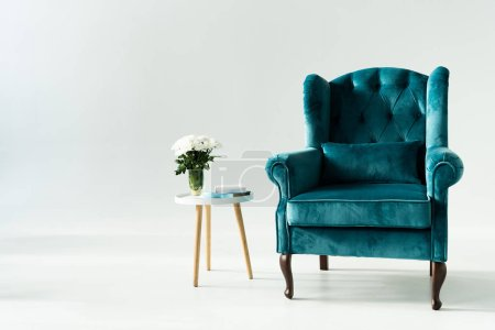 Photo pour Fauteuil turquoise par table basse avec fleurs et livres sur fond gris - image libre de droit
