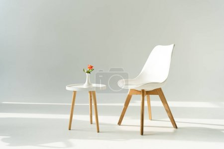Photo for White trendy chair by table with rose in vase on grey background - Royalty Free Image