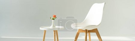 Photo for Panoramic shot of modern chair by table with rose in vase on grey background - Royalty Free Image