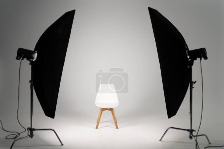 White modern chair with studio light on grey background