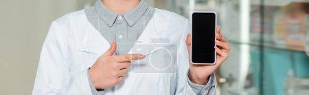 Photo pour Vue recadrée du pharmacien pointant du doigt le smartphone avec écran blanc, prise de vue panoramique - image libre de droit