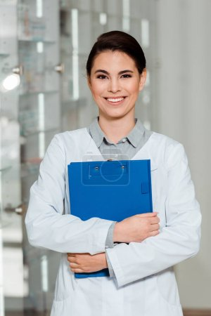 Photo for Attractive pharmacist with clipboard smiling at camera in apothecary - Royalty Free Image