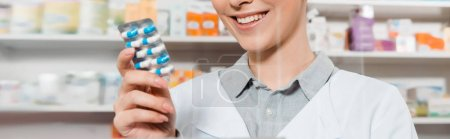 Cropped view of smiling pharmacist holding pills in drugstore, panoramic shot