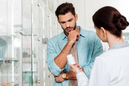 Photo pour Concentration sélective d'un client et d'un pharmacien débordant de connaissances, avec des pilules en apothicaire - image libre de droit