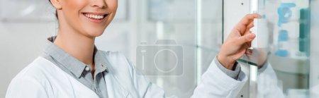 Photo pour Vue recadrée du pharmacien souriant par vitrine, vue panoramique - image libre de droit